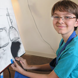 boy drawing with charcoal on canvas